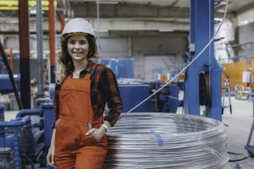 Portrait of young happy apprentice machine operator woman checking component in a factory with white helmet smiling to camera and sitting in a large shipping manufacturing facility warehouse at metal cable factory XXXL